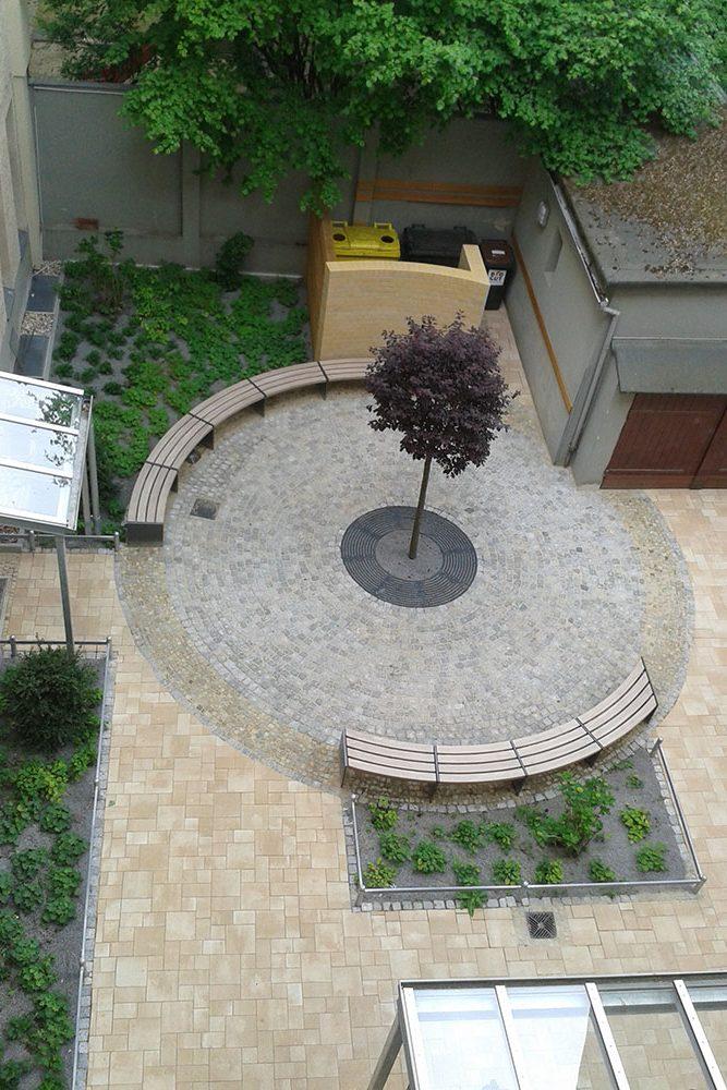Hofgestaltung – Sitzbänke um einen neuen Hofbaum herum