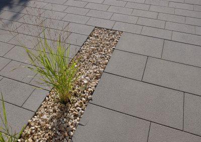 Terrassenbelag aus Steinplatten und angrenzenden Kiesflächen