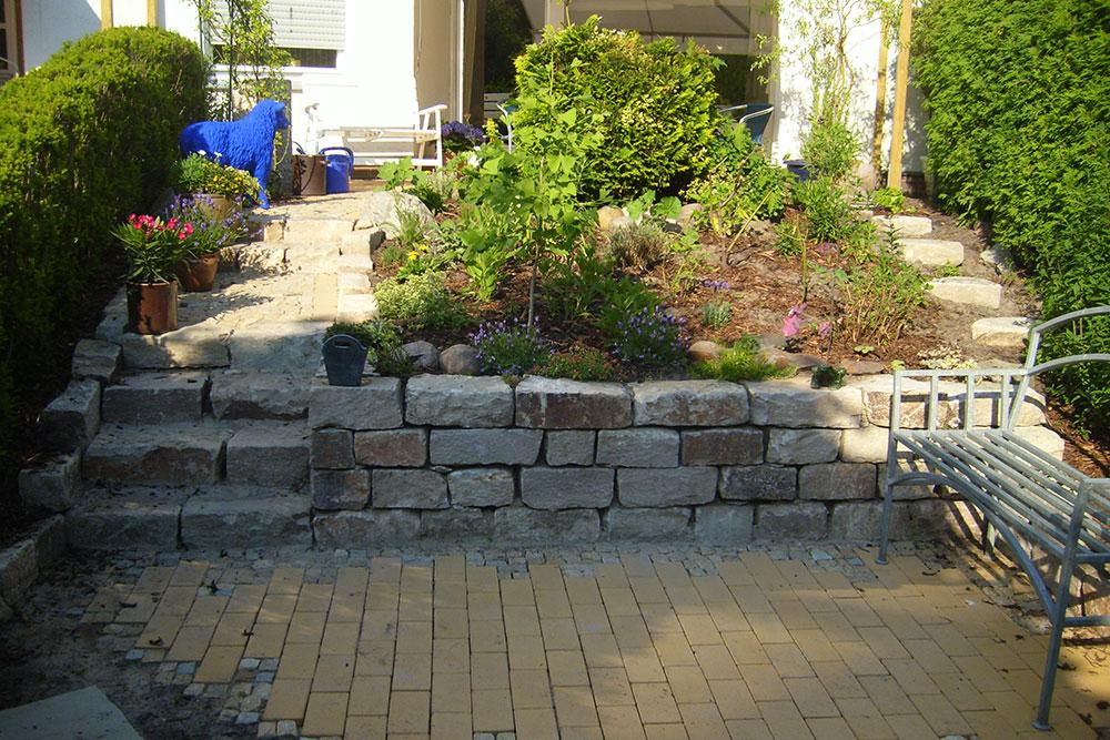 Trockenmauer und Stufen aus Naturstein in einem terrassierten Privatgarten