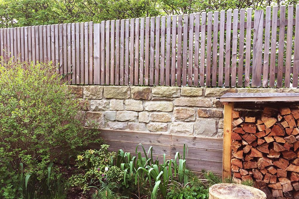 Holzzaun auf Mauer aus Natursteinquadern
