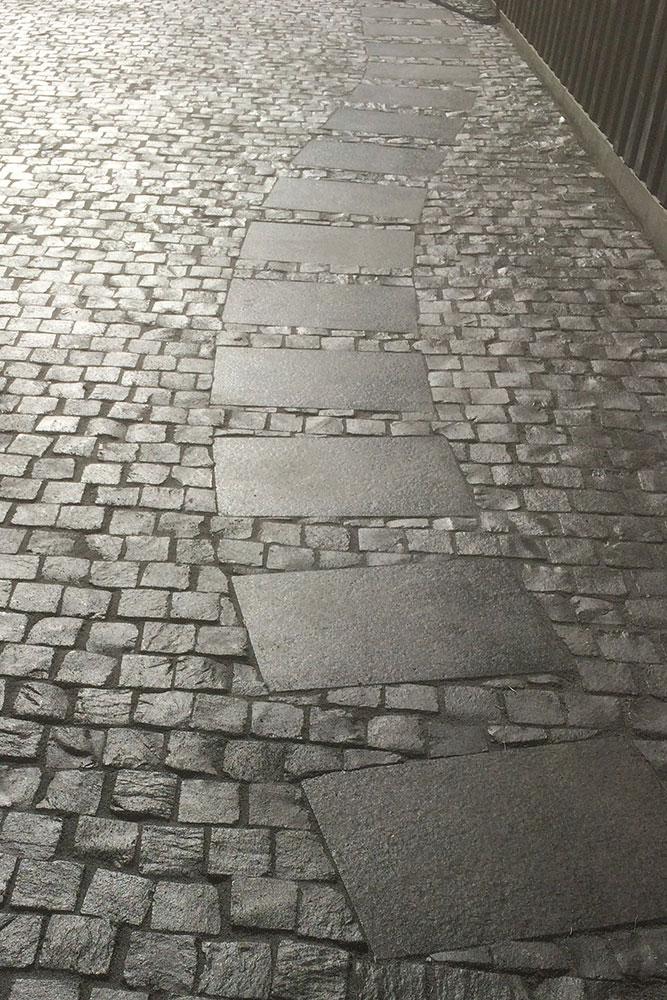 elegante Zufahrt aus dunklem Natursteinpflaster mit eingelegten Platten