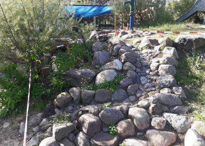 Umgestaltung einer vorher eintönigen Spielfläche zu einem abwechslungsreichen Spielgarten. Großzügige Geländemodellierung, Kletterhügel mit Pumpe und Bachlauf