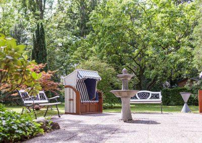 professionelle Gartenpflege eines Hotelgartens: Rasenfläche, Hecken, Stauden- und Rosenrabatten, repräsentativer Eingangsbereich