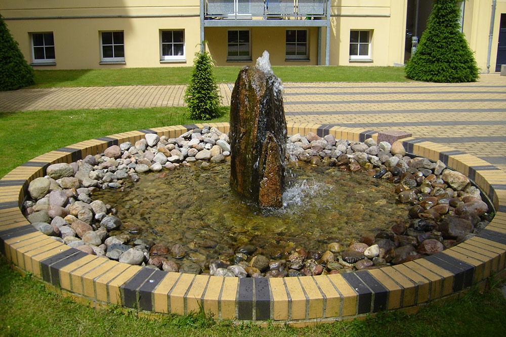 Natur- und Betonsteinflächen, Pflanz- und Rasenarbeiten, Spielflächen, Mülleinhausung und Fahrradstellplätze