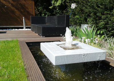Loungebereich mit formalem Wasserspiel in einem kleinen Garten