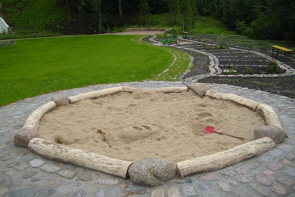 Sandkasten mit Einfassung aus Baumstämmen und Naturstein