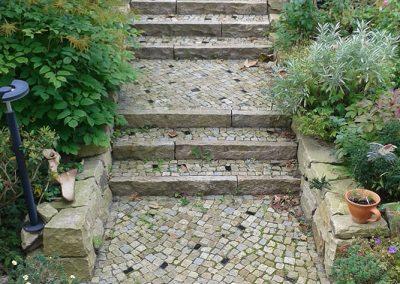 Mauern aus Bad Karlshafener Sandstein-Quadern, Stufen aus Granitkantensteinen grau-gelb und Granit-Mosaik, grau-gelb mit anthrazit-farbenen lasierten Einlegern