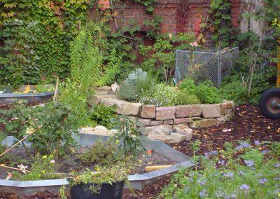 Neubau eines Schulgartens: Anlage von Kräuter- und Blumenbeeten auf einem Schulhof, spielerisch gestalteter Schutzzaun aus Holz
