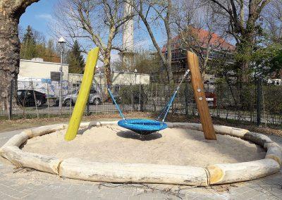 Sandspielbereiche mit liegenden geschliffenen Robinienstämmen eingefasst, sowie Nestschaukel (Fa. Eibe) für Kleinkinder