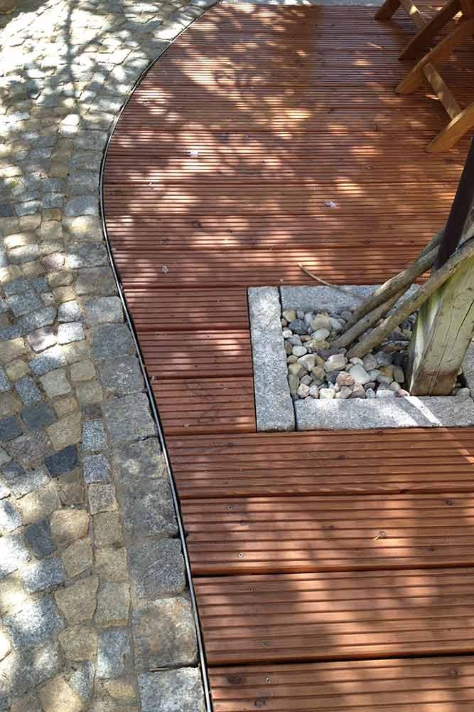 Stahlband zwischen Holzterrasse und Natursteinmosaikpflaster